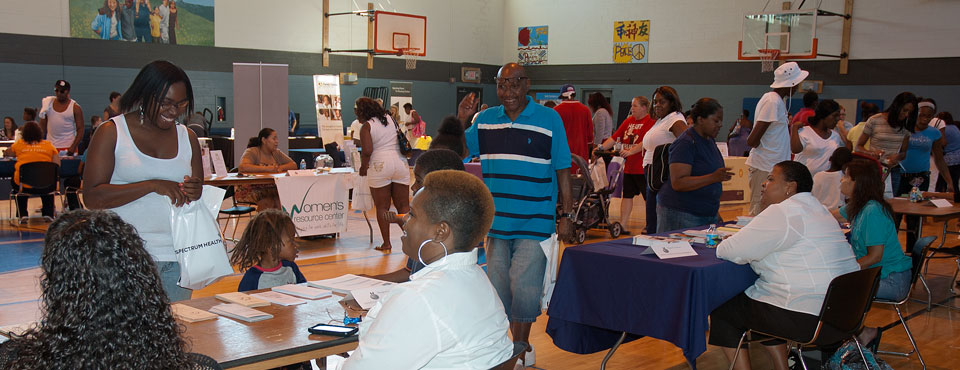 Resource Fair attendees visit information tables staffed by community organizations