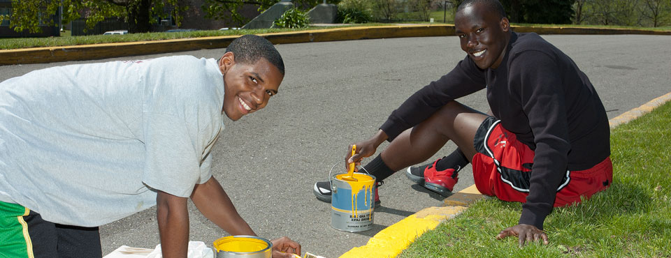 two young men painting curb at GRHC administrative office