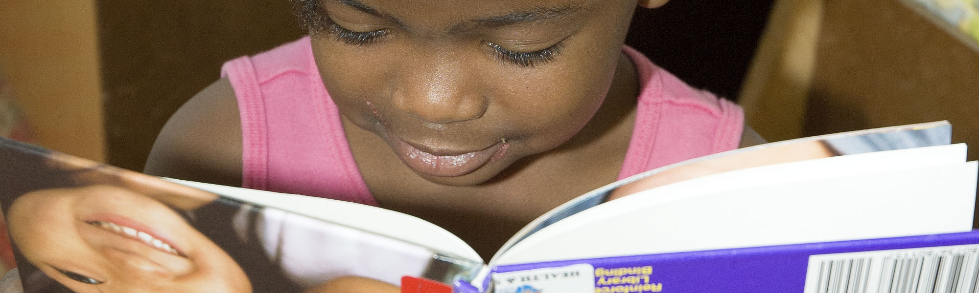 little girl reading a book upside down